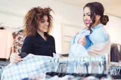 Blick mit zwei jungen Mädchen auf Kleidung im Speicher Lizenzfreie Stockfotos