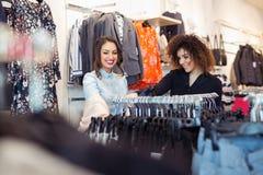 Blick mit zwei jungen Mädchen auf Kleidung im Speicher Lizenzfreie Stockfotografie