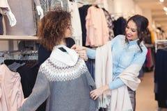 Blick mit zwei jungen Mädchen auf Kleidung im Speicher Lizenzfreie Stockbilder