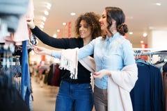 Blick mit zwei jungen Mädchen auf Kleidung im Speicher Lizenzfreies Stockbild