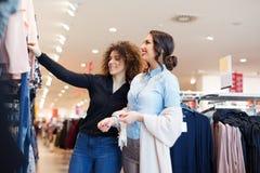 Blick mit zwei jungen Mädchen auf Kleidung im Speicher Stockfotografie