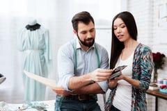 Blick mit zwei Modedesignern auf Zeichnung und Muster Lizenzfreies Stockfoto