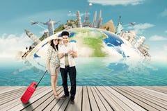 Blick mit zwei Touristen auf Weltkarte auf Tablette Stockbild