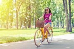 Blickar för den snygga kvinnan som är lyckliga under hennes cykel, rider i PA Royaltyfria Foton