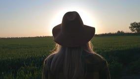 Blickar för en älskvärd för ung kvinna handelsresande eller bondepå solnedgången eller soluppgången Bärande plädskjorta och hatt  lager videofilmer