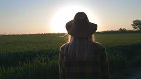 Blickar för en älskvärd för ung kvinna handelsresande eller bondepå solnedgången eller soluppgången Bärande plädskjorta och hatt  stock video