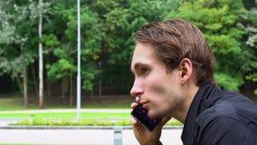Blickar för ung man på samkvämmen knyter kontakt i smartphonen som lutar över räcket av bron lager videofilmer