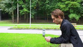 Blickar för ung man på samkvämmen knyter kontakt i smartphonen som lutar över räcket av bron parkerar in stock video