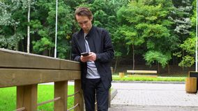 Blickar för ung man på samkvämmen knyter kontakt i smartphonen som står på bron parkerar in lager videofilmer