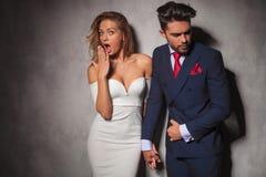 Blicke der eleganten Frau beim Halten der Hand ihres Mannes sehr überrascht Stockfotografie
