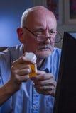 Blicke des älteren Mannes beim Wieder füllen der Verordnung betroffen on-line, vertikal Lizenzfreies Stockfoto