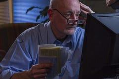 Blicke des älteren Mannes gesorgt, wie er die Lohnlisten, die on-line sind, horizontal Lizenzfreies Stockfoto
