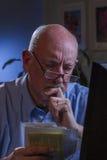 Blicke des älteren Mannes gesorgt, wie er die Lohnlisten, die on-line sind, vertikal Stockfoto