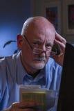 Blicke des älteren Mannes gesorgt, wie er die Lohnlisten, die on-line sind, vertikal Lizenzfreies Stockfoto