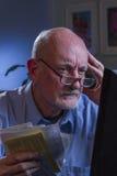 Blicke des älteren Mannes gesorgt, wie er die Lohnlisten, die on-line sind, vertikal Stockbild