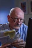Blicke des älteren Mannes gestört, wie er die Lohnlisten, die on-line sind, vertikal Stockbilder
