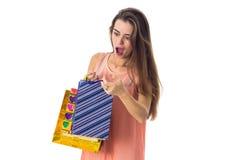 Blicke des jungen Mädchens überrascht an den Geschenktaschen lokalisiert auf weißem Hintergrund Stockfotografie