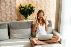 Blicke des jungen Mädchens zu Hause überrascht am Laptop Lizenzfreie Stockbilder
