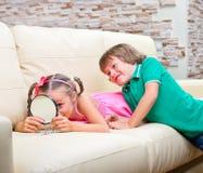 Blicke des kleinen Mädchens und des Jungen in einem Spiegel Stockfotos