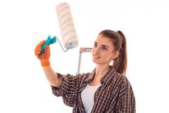 Blicke eines jungen Mädchens weg und angehobene in der Hand Rolle für die malende Wandnahaufnahme lokalisiert auf weißem Hintergr Lizenzfreie Stockbilder