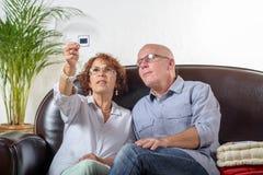 Blicke eines schieben ältere Paares auf eine Fotografie Stockbild