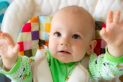 Blicke mit einen hebt die jährigen Babys und Griffe oben an Kleiner netter Junge in einer hellgrünen Klage mit Schafen lizenzfreies stockfoto