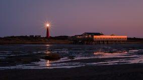 Blicken in Richtung des Schiermonnikoog-Leuchtturmes vom Strand nach Sonnenuntergang Stockfoto