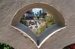 Blicken am Stadtverkehr durch Gebäudegestaltungselement Lizenzfreie Stockfotografie