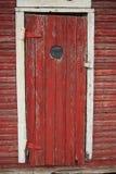 Blickloch in der alten roten Tür Stockfotografie
