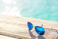 Blie Sunglasses on wooden decking by seaside Stock Photo