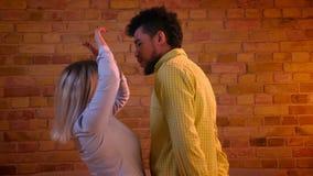 Blij Afrikaans kerel en blonde Kaukasisch meisje die flirtingly met elkaar in romantische en comfortabele atmosfeer dansen stock videobeelden