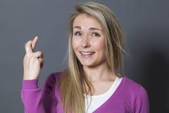 Blij blond meisje het vertrouwen op geloof in vast de kruising van haar vingers Royalty-vrije Stock Afbeelding