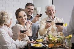 Blij familie het vieren diner stock afbeeldingen