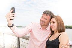 Blij jong houdend van paar die selfie op camera maken terwijl in openlucht status stock afbeeldingen