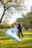 Blij jong paar die pret in bloeiende de lentetuin hebben Liefde en romantisch thema Royalty-vrije Stock Afbeelding