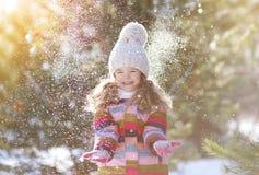 Blij kind die pret met sneeuw hebben Stock Foto's