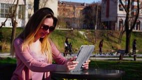 Blij maak meisje die tot videovraag maken door tablet aan vriend in park en hand golven stock video