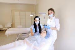 Blij maak vrouw permanent krijgen maken omhoog bij de kosmetiekkabinet door dermatoloog Royalty-vrije Stock Foto's