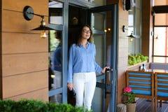 Blij maak vrouwelijke klant die restaurant met dichte omhooggaande satisfi verlaten Stock Afbeeldingen