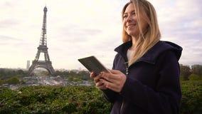 Blij maak vrouwelijke persoon die door tablet dichtbij de Toren van Eiffel doorbladeren stock video