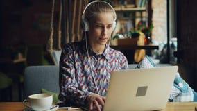 Blij meisje die aan muziek in hoofdtelefoons luisteren die laptop het typen het zingen in koffie gebruiken stock footage