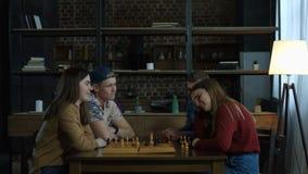 Blij meisje die haar vriend in schaakspel verslaan stock footage