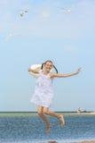 Blij meisje die over het water bij het strand springen stock fotografie