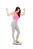 Blij meisje die zich op een gewichtsschaal bevinden Royalty-vrije Stock Afbeelding