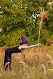 Blij meisje in heksenkostuum het praktizeren yoga Stock Afbeeldingen