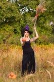 Blij meisje in heksenkostuum met bezemsteel Stock Afbeelding