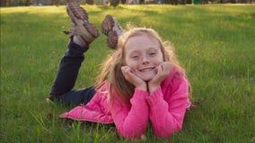 Blij onbezorgd meisje die op gras liggen en in de zomerpark glimlachen stock videobeelden