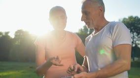 Blij oud paar dat hun telefoon in het park met behulp van stock video