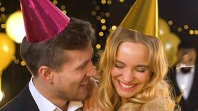 Blij paar die en aan de partij blazende partij-ventilator van de cameraverjaardag lachen kijken stock video
