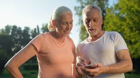 Blij sportief oud paar die slimme telefoon in het park met behulp van stock videobeelden